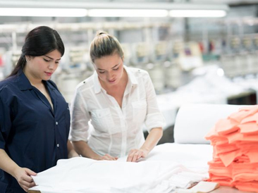 Two women touching a piece of a cotton fabric at a factory