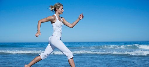 A blond girl wearing white cotton cloths walking on the beach