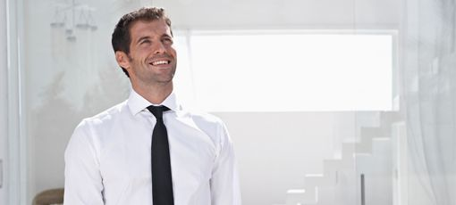 Happy man smiling wearing a formal white cotton shirt with a black tie