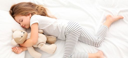 A little girl sleeping and hugging a teddy bear on a bed with white cotton bedding