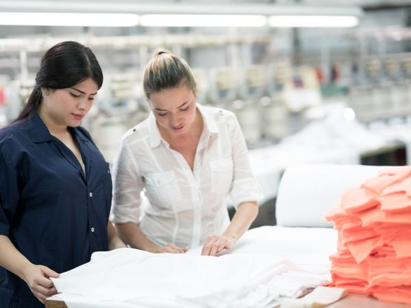 2 women touching a cotton fabric at a factory