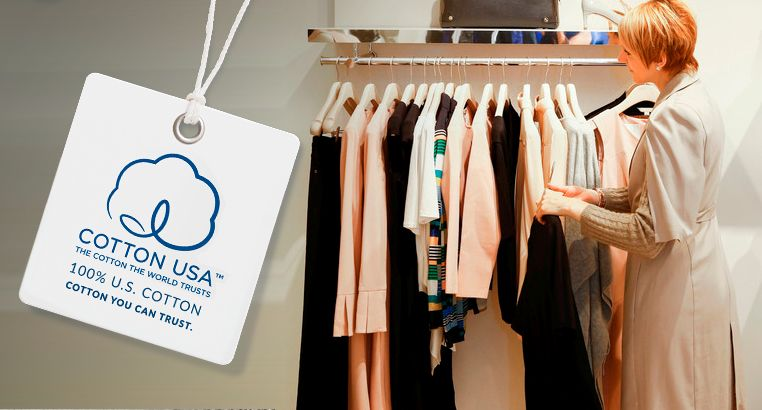 A woman looking at several cotton blouses and sweaters, a big COTTON USA tag is on the left