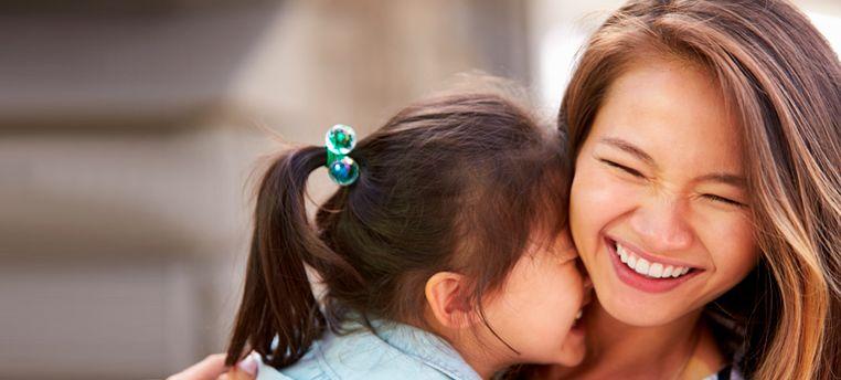 Asian little girl hugging mom, both smiling