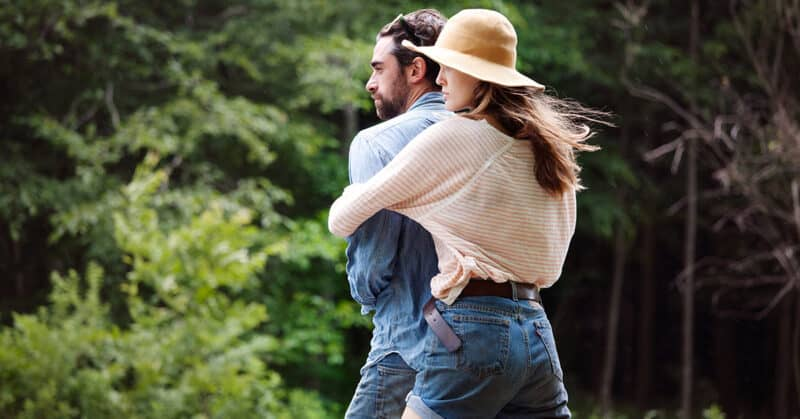 a girl with cotton blouse hugging a guy from behind outdoors